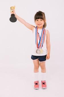 한 손으로 트로피를 들어올리는 스포츠 챔피언 메달을 가진 작은 갈색 머리 소녀. 스포츠와 승리 개념