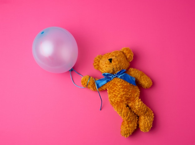 Little brown teddy bear holding a blue inflated balloon