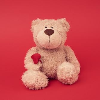 Маленький коричневый плюшевый мишка, игрушка сидит на красной поверхности