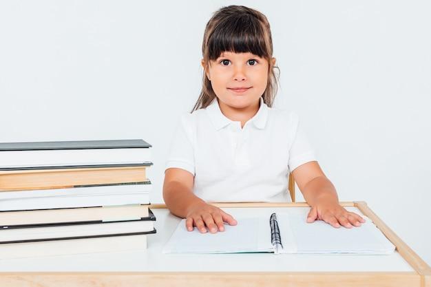 책과 함께 의자에 앉아 학교에서 갈색 머리 소녀
