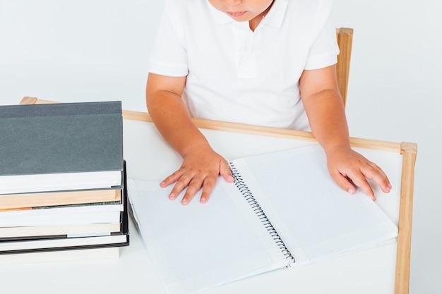 미소, 책과 함께 의자에 앉아 학교에서 작은 갈색 머리 소녀
