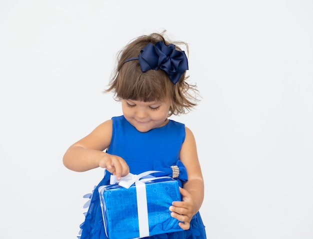 Little brunette girl in blue dress unties gift box