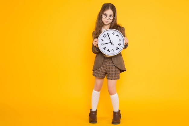 Little brunette girl in costume with clocks