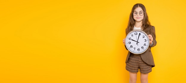 Little brunette girl in costume with clocks