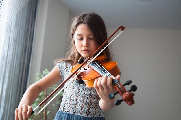 Маленькая брюнетка девушка в красивом платье играет на скрипке в помещении концепция музыкальных инструментов