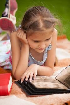 Маленькая брюнетка девочка, лежа в парке и глядя на семейный фотоальбом
