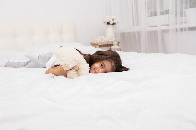 Little brunette girl lying with teddy bear on bed at home.