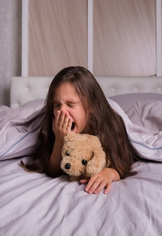 A little brunette girl in pajamas lies on the bed linen on the bed with a teddy bear and yawns