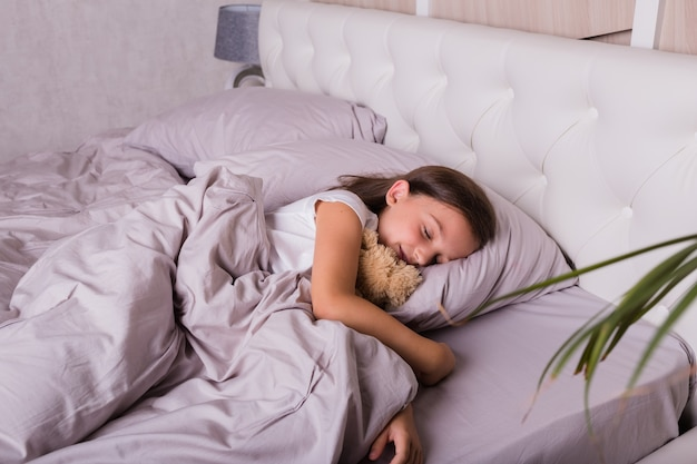 A little brunette girl in pajamas sleeps with a soft toy on the bed in the bedroom