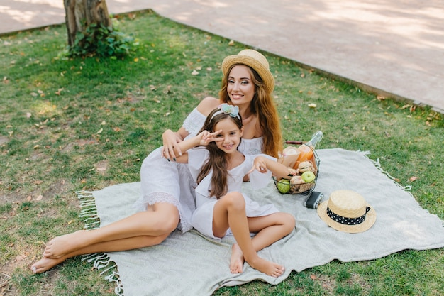 Little brunette girl posing on blanket showing peace sign with excited smile. outdoor portrait of pretty woman and her daughter lying on the ground with basket of apples.