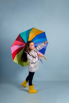 A little brunette girl in a raincoat and rubber boots stands under a multicolored umbrella on a blue background with a place for text