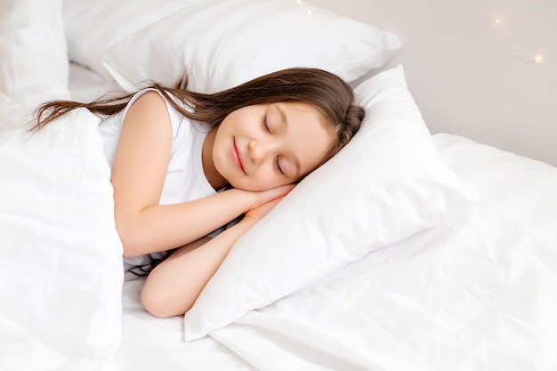 Little brunette girl sleeps sweetly in bed with white linen. space for text. healthy baby's sleep