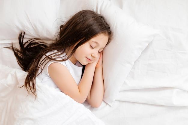 작은 갈색 머리 소녀 흰색 리넨과 함께 침대에서 상쾌하게 잔 다. 텍스트를위한 공간입니다. 건강한 아기의 수면