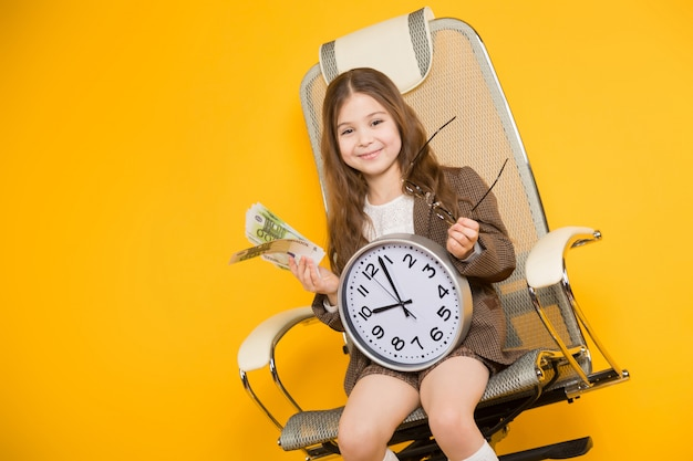 Little brunette girl with clocks and cash in chair