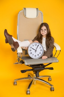 Little brunette girl with clocks in chair