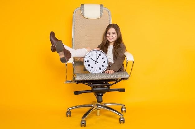 Little brunette girl with clocks in chair