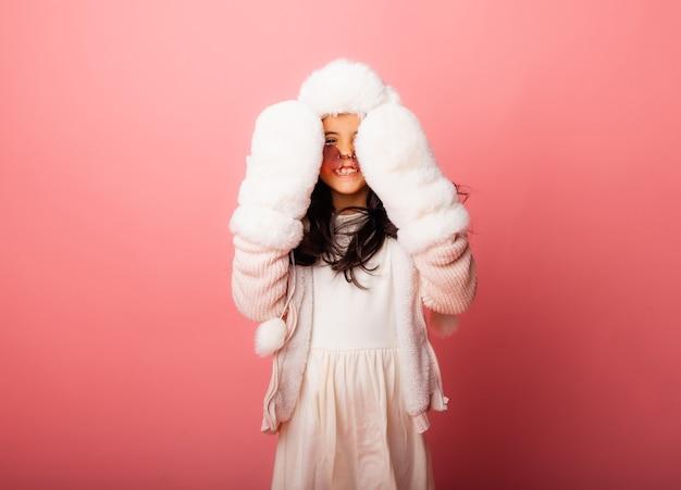 Маленькая девочка брюнетки с длинными волосами в зимней меховой шапке и рукавицах на розовом фоне.