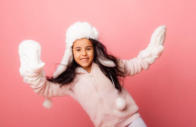 Маленькая брюнетка с длинными волосами в зимней шапке и варежках на розовом фоне