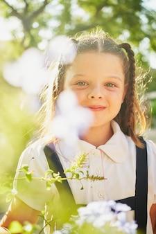 小さなブルネットのスペインの女の子は、カメラに微笑んで植物と花の間に立っています