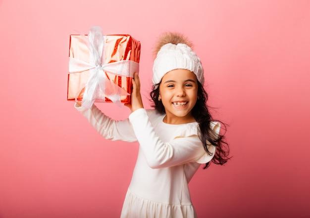 겨울 모자에 긴 머리를 한 작은 갈색 머리는 분홍색 배경에 선물을 들고 있습니다.