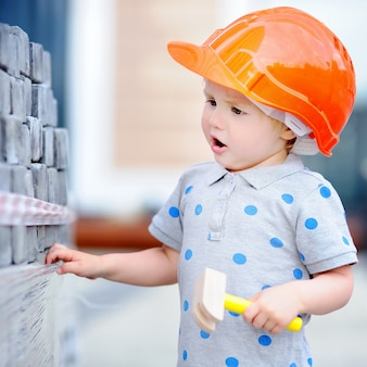 Little builder in hardhats with hammer working outdoors