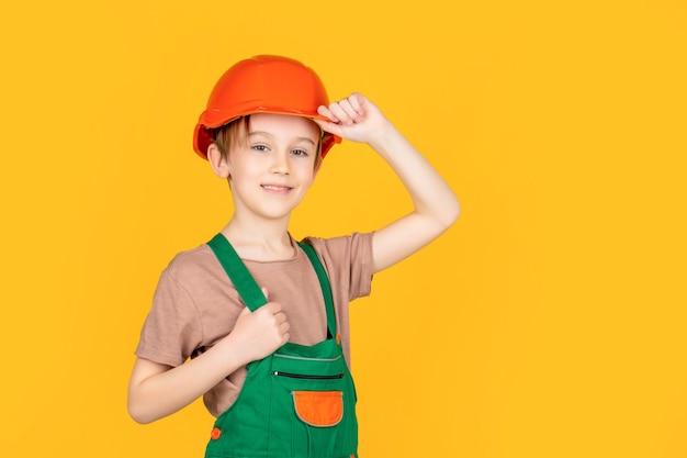 헬멧에 작은 작성기. 워커 빌더로 분장한 아이. 헬멧을 쓰고 어린 소년입니다. 안전모에 세로 작은 작성기. 어린이 건물 헬멧, 안전모.