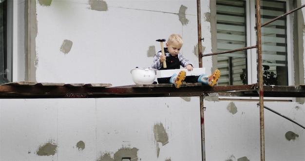 小さなビルダーが足場に座っているハンマーで発泡スチロールの一部をノックして叩きます