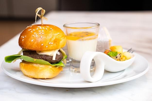 Маленький бургер и пудинг из маракуйи в стакане с фруктовой смесью и бутерброд в обертках на белом блюде на время семинара.