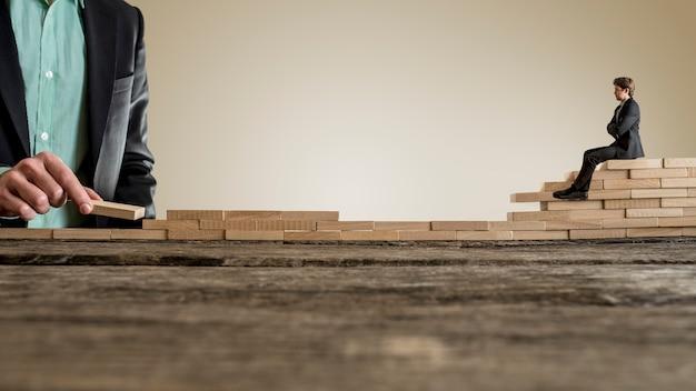 木製のレンガの壁に座っているスーツの小さな実業家