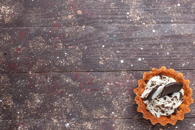 木製の茶色の素朴な、ケーキビスケットの甘い焼きで分離されたクリームとチョコレートの小さなケーキ