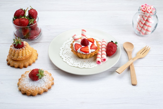 クリームとスライスしたイチゴの小さなケーキ白のキャンディー、フルーツケーキベリーの甘い砂糖
