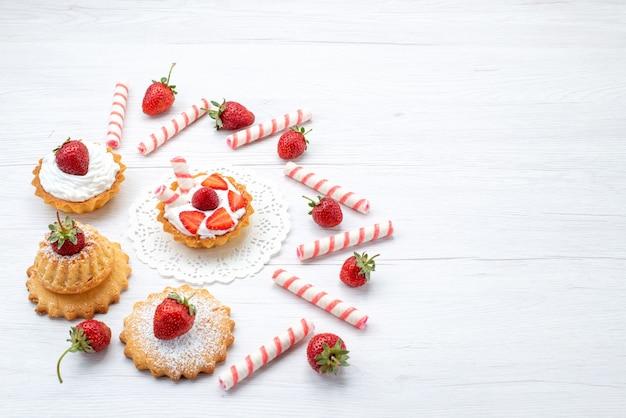 Piccola torta con crema e fragole a fette caramelle sulla scrivania bianca, torta di frutta bacca zucchero dolce