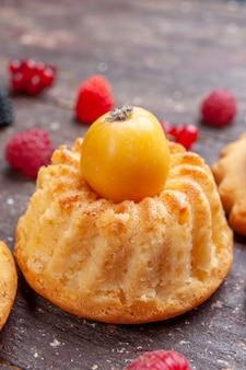 Piccola torta con ciliegia gialla su marrone, biscotto da forno ai frutti di bosco