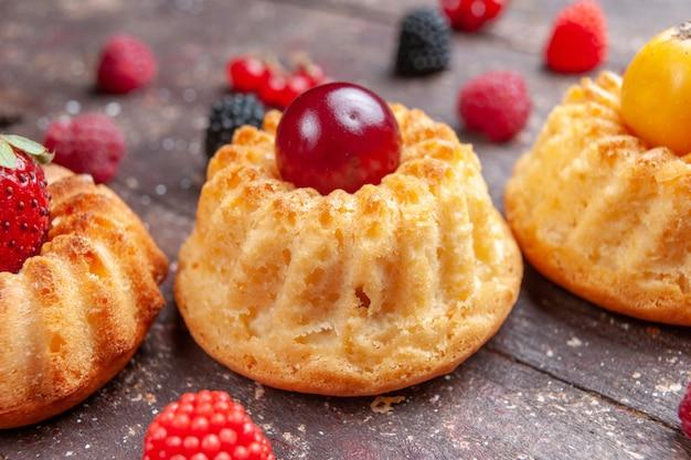 Маленькие пирожные со свежими фруктами на коричневом ягодном бисквите