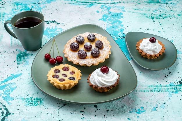 緑のプレートの中に果物が入った小さなケーキと、青のお茶とシナモン、お茶の甘いケーキ焼きパイ