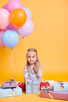 Little casual cutie with gift posing on yellow wall in isolation during her birthday party