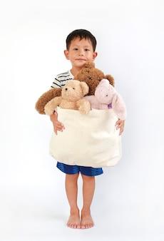 白い背景の上の寄付のためのおもちゃのバッグを保持している小さな白人の男の子。他の人に幸せを渡し、コンセプトを共有する