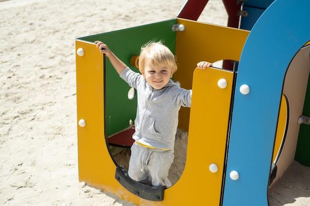 화창한 가을 날 어린이 놀이터에서 노는 백인 금발 소년.