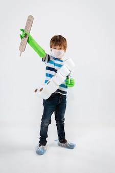 フェイスマスク、消毒剤、温度計、トイレットペーパーのバンドラーを持った、コロナウイルスのパンデミックと戦う戦士としての白人の少年。人間の生命のための戦争のティーンボーイ。子供の頃、健康の概念。