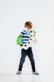 Маленький кавказский мальчик как воин в борьбе с пандемией коронавируса, со щитом, копьем и туалетной бумагой, атакующий, атакующий