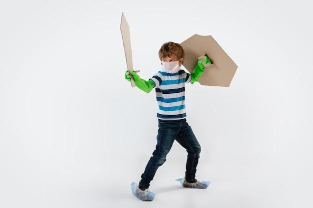 盾、剣、トイレットペーパーの装弾ベルトを持った、コロナウイルスのパンデミックと戦う戦士としての白人の少年。人間の生命のための戦争のティーンボーイ。子供の頃、健康、勝利の概念。