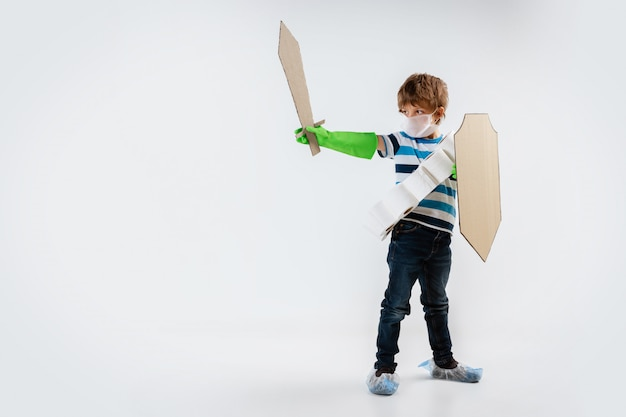 Little caucasian boy as a warrior in fight with coronavirus pandemic, with a shield, a spear and a toilet paper bandoleer, attacking
