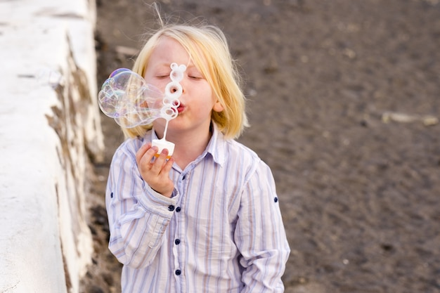 ビーチでシャボン玉を吹く小さな白人の少年。休暇中に遊んでいる少年。ビーチで泡の杖を使用してシャボン玉を遊んで吹くシャツのかわいい無邪気な少年