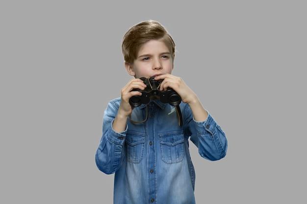 쌍안경을 사용하는 어린 백인 소년. 회색 배경 쌍안경을 들고 데님 재킷에 귀여운 소년.
