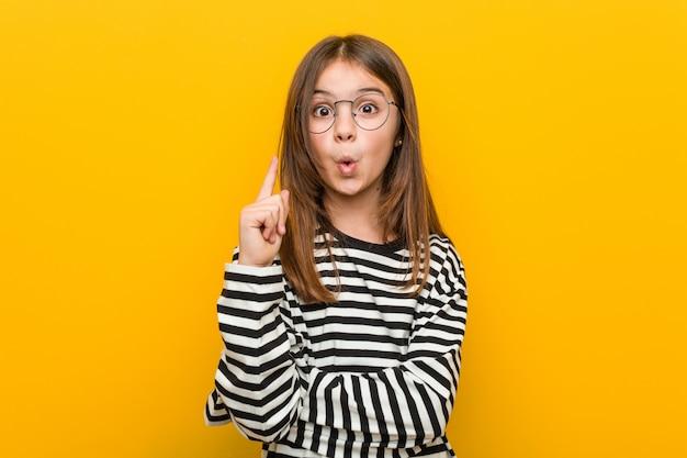 Маленькая кавказская милая девушка имея некоторую отличную идею, концепцию творческих способностей.