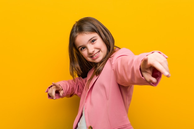 Little caucasian cute woman cheerful smiles pointing to front.
