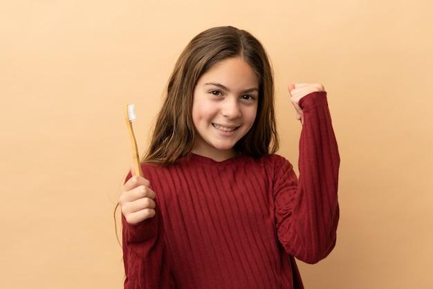 Маленькая кавказская девочка чистит зубы на бежевом фоне, празднует победу