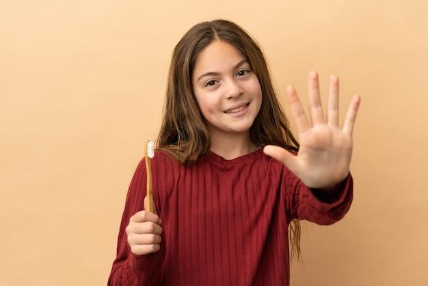 Маленькая кавказская девочка чистит зубы на бежевом фоне, считая пять пальцами