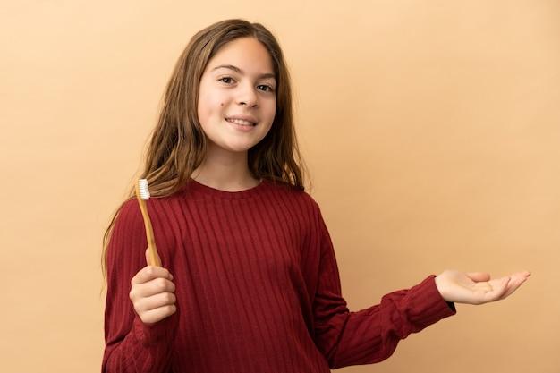 ベージュの背景で隔離された彼女の歯を磨く小さな白人の女の子は、来て招待するために手を横に伸ばします