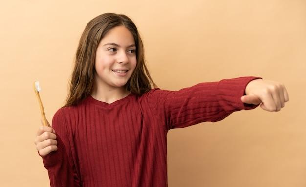 Маленькая кавказская девушка чистит зубы на бежевом фоне и показывает жест рукой